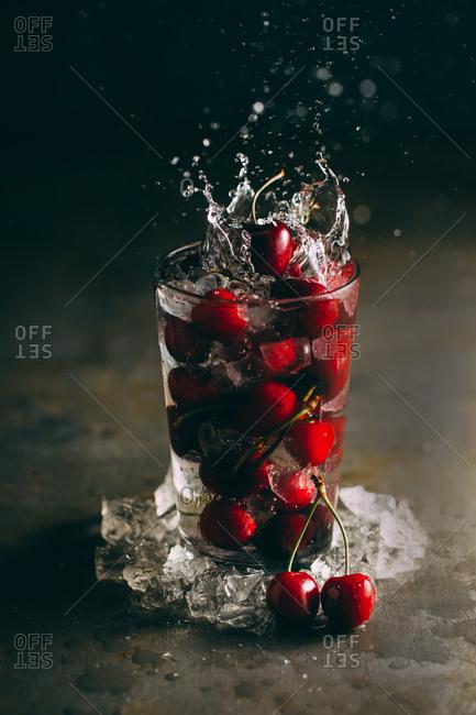 Splashing cherries in a glass with ice on dark background