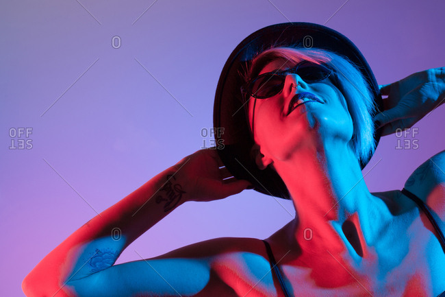 Attractive woman with hat shoot in studio with blue and red lights