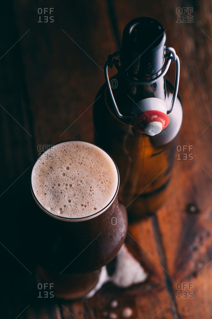 Stout beer in glass and bottle on dark background