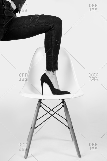 Woman with her foot posing in a design chair with high heels