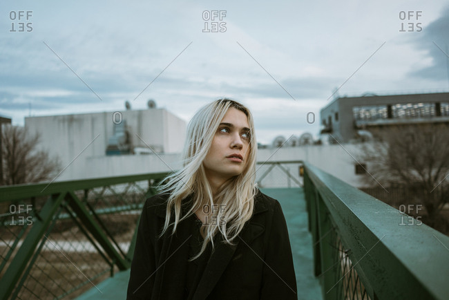 Young woman walking on pedestrian bridge