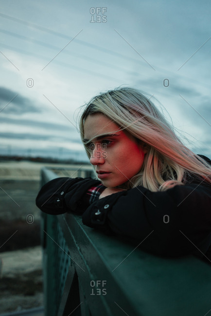 Woman leaning on fence in evening
