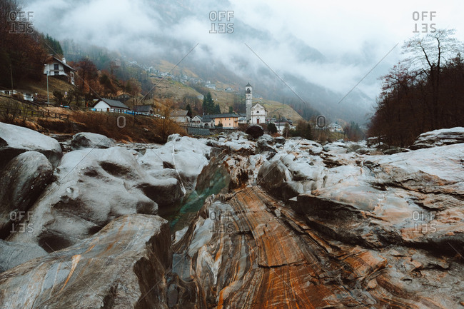 View to wet rocks and small mountain town in foggy day.