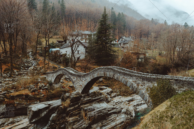 Small stone-made wavy bridge in the village in autumn.