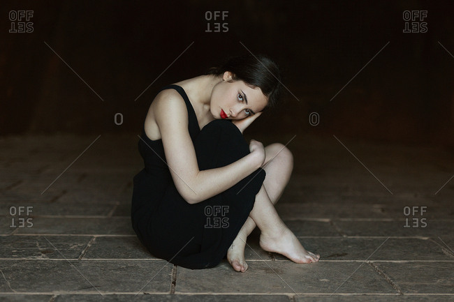 Beautiful graceful brunette with red lipstick in black dress sitting barefoot on floor and looking at camera on black background