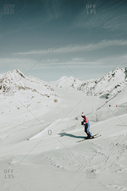 Side view of unrecognizable sportsman riding snowboard on snowy mountain in winter.
