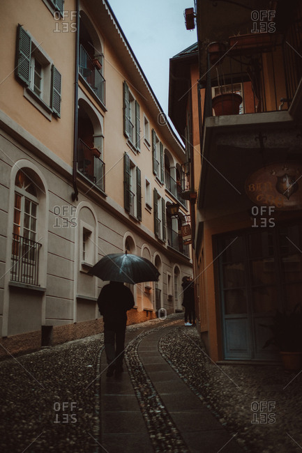 July 3, 2018: Cannero Riviera, Italy, back view of unrecognizable man walking with umbrella on town street in rainy day.