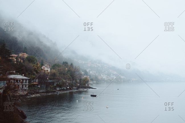Small fishing boat in lake at village houses in foggy day.