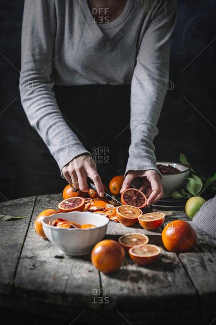 Crop person peeling blood oranges