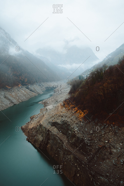 Small blue river flowing between two hills in autumn foggy day.