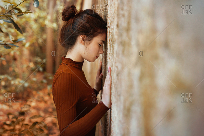 Side view of tranquil thin brunette with close eyes in brown dress leaning forehead and hands against wall