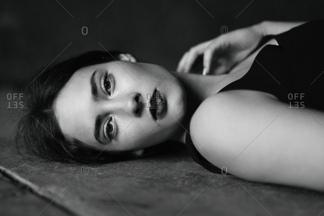 Black and white shoot of beautiful brunette lying on floor and looking at camera on black background