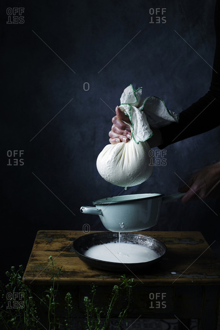 Crop hands of cook preparing to squeeze the cottage cheese on a table.