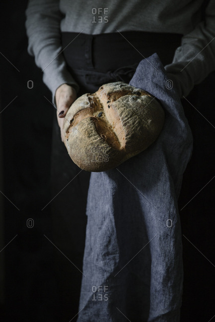 Crop hands of unrecognizable person standing with bread.