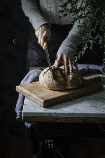 Crop hands of unrecognizable person standing at the table and cutting bread.