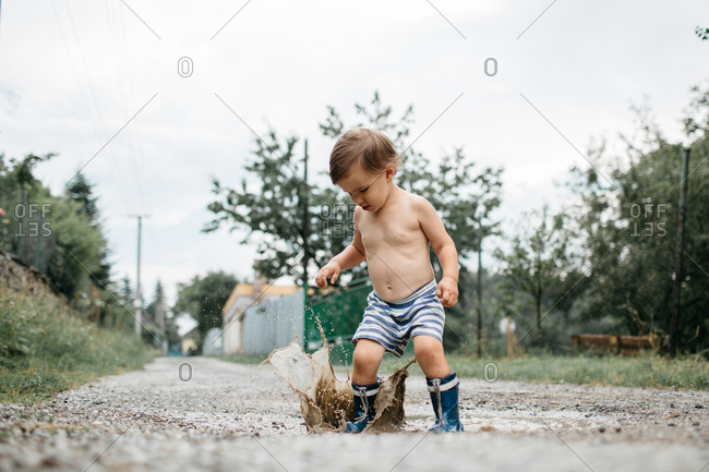 Ground angle shot of a shirtless child in wellies playing in a mud puddle on a summer day. Portrait of a toddler boy in rain boots jumping puddles on the road after the rain.