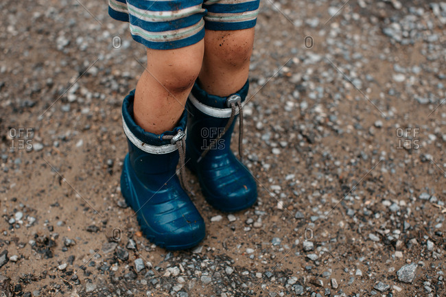 Cropped image of a child in rubber rain boots covered in dirt and mud. Close up of dirty bare legs of a toddler boy wearing wellington boots.