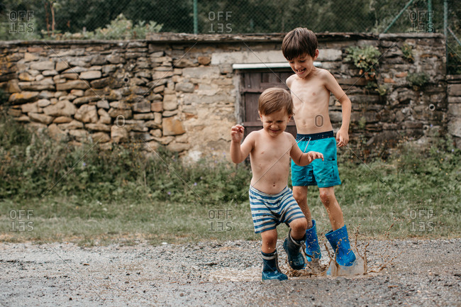 Two children wearing wellington boots playing in a mud puddle on a summer day. Shirtless brothers in rain boots jumping puddles after the rain.