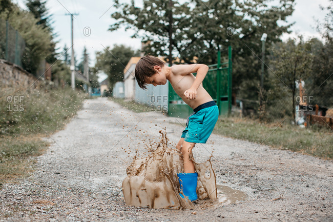 Portrait of a shirtless child in wellies splashing around in a mud puddle on a summer day. Happy boy in rain boots having fun jumping puddles on the road after the rain.