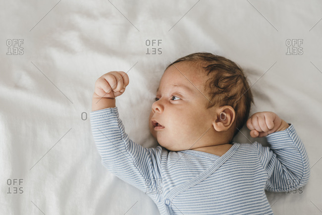 Newborn baby stretching his arms on bed