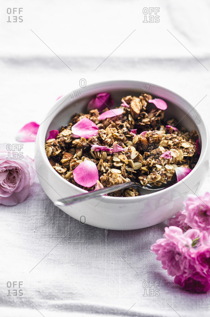 Almond and rose granola in handmade bowl on linen.
