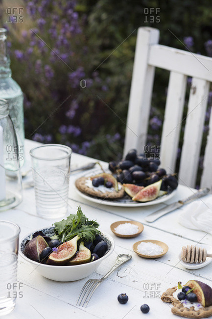 Outdoor summer dinner: fresh salad with figs and red grapes on white rustic table