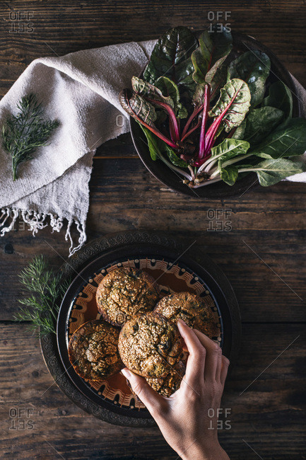 Hands holding Corn muffins bread with leaf of chard