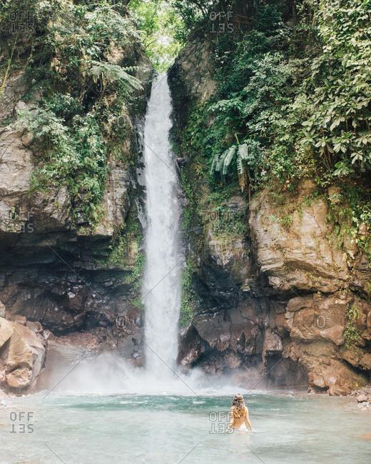Girl enjoying Katibawasan Fallsin Philippines island of Camiguin