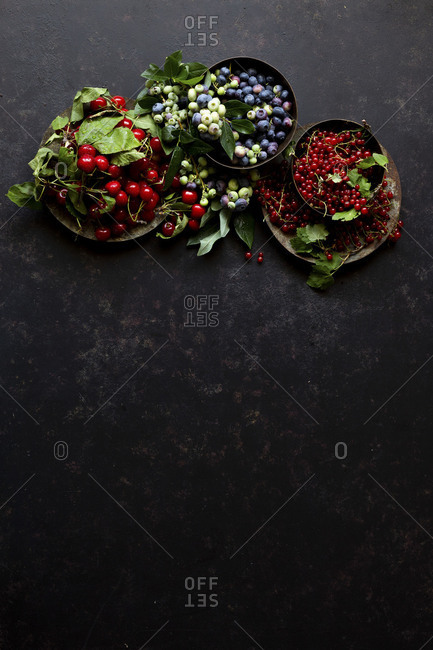 Assortment of Summer fruits on a black textured surface
