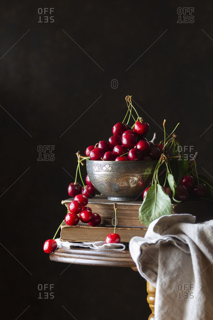 Still life of sweet farm fresh cherries with leaves on books