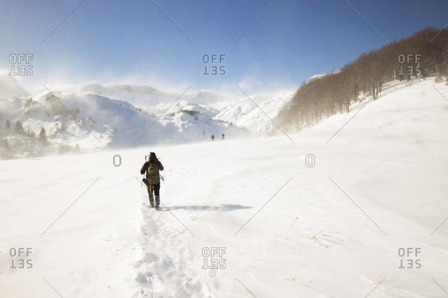 Man hiking trough snowstorm