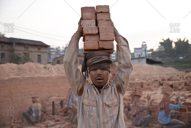 Kathmandu, Nepal - February 19, 2015: Construction worker balancing two tall piles of bricks on head