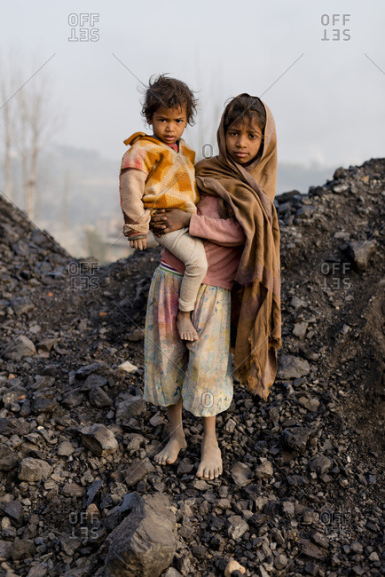 Kathmandu, Nepal - February 20, 2015: Young girl draped in garments carrying smaller child through rubble
