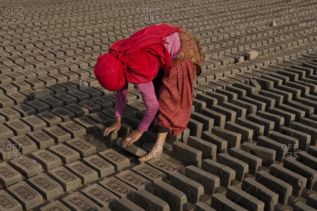 Female manual worker kneeling forward to adjust bricks