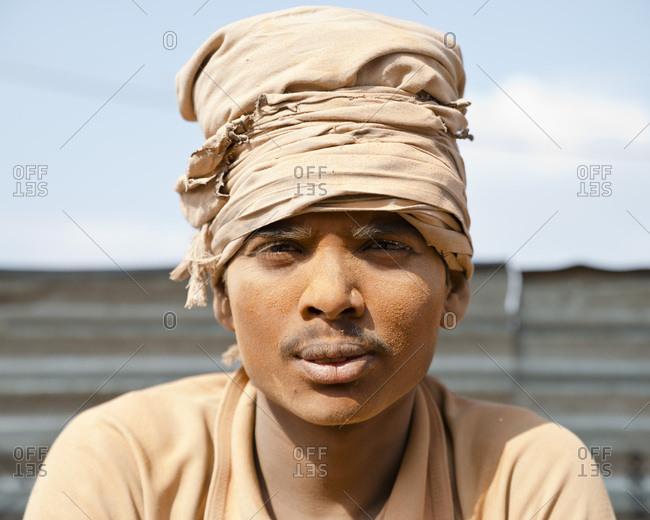 Kathmandu, Nepal - February 19, 2015: Portrait of worker with dust caked on face in sunlight