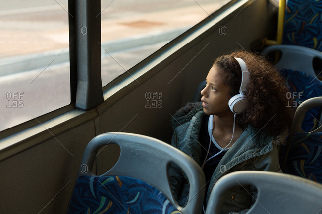 Teenage girl listening music on headphones while travelling in the bus