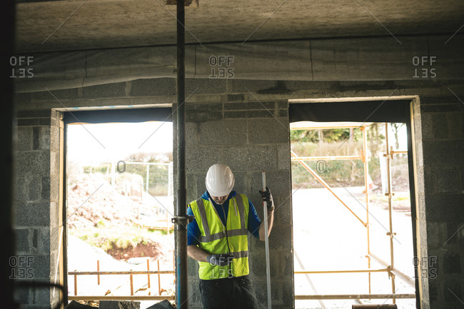 Engineer with level gauge using his phone at the construction site