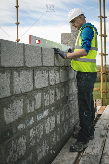 Engineer doing a level check on the wall at construction site