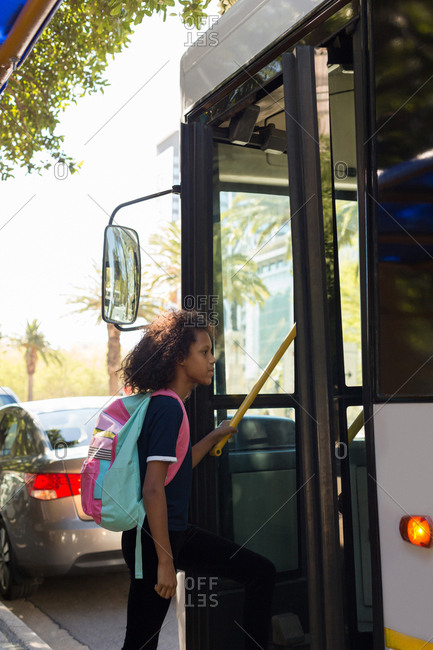 Teenage girl boarding bus at street