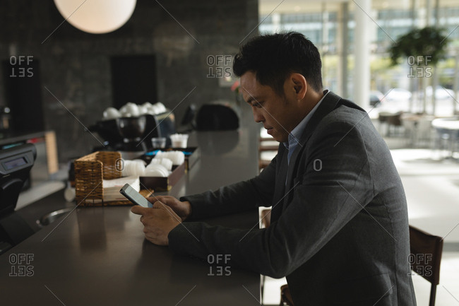 Businessman using his phone at the cafeteria counter in office