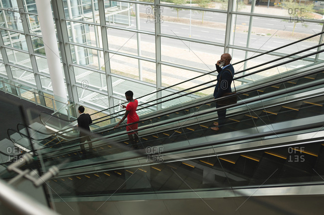 Three businesspeople going down on an escalator in the office