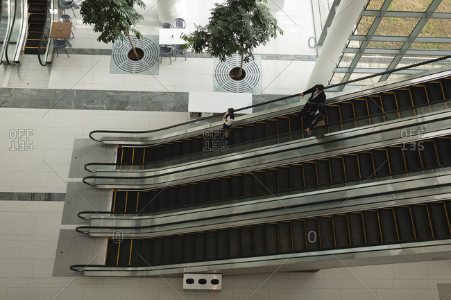 Businesspeople going down on an escalator in office