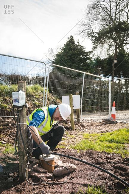 Builder installing a water pump in garden
