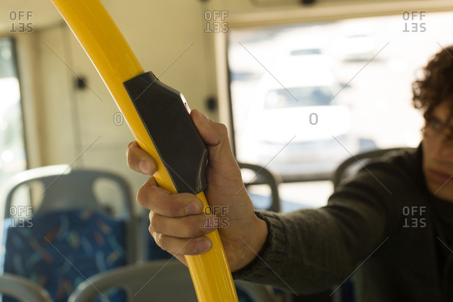 Man pressing button on pole while travelling in the bus