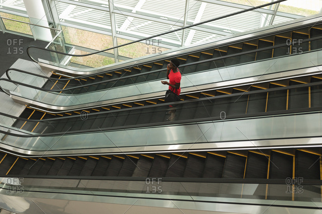 Businesswoman talking on the phone while going down on an escalator in office