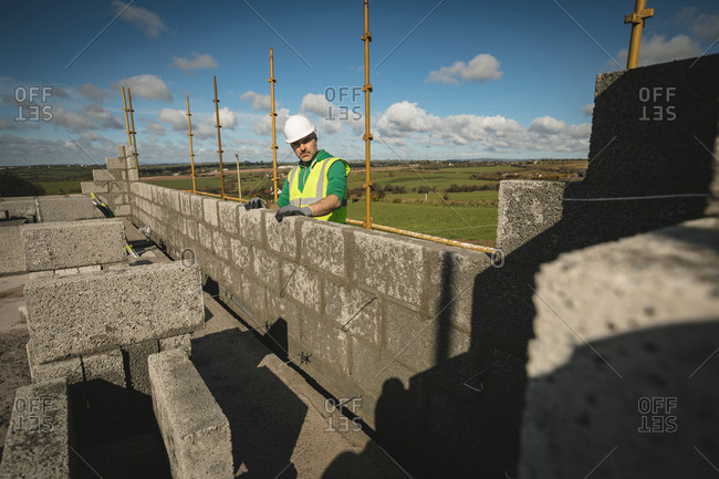 Engineer standing against the wall at construction site on a sunny day