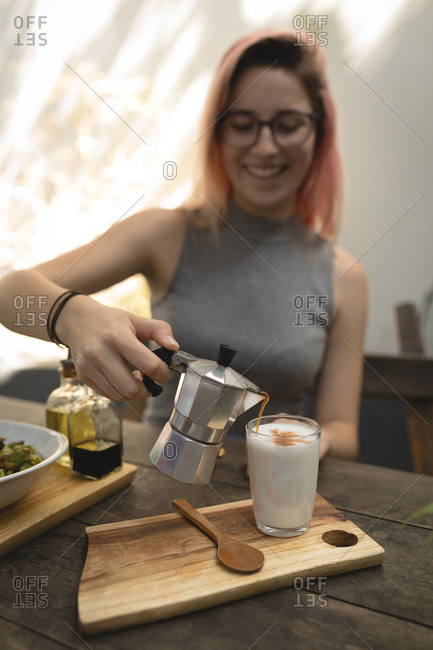 Young woman pouring coffee from a coffee kettle