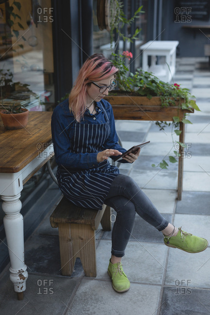 Young woman using a tablet outside coffee shop