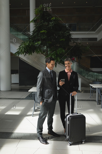 Smiling businesspeople with suitcase looking at the phone in office