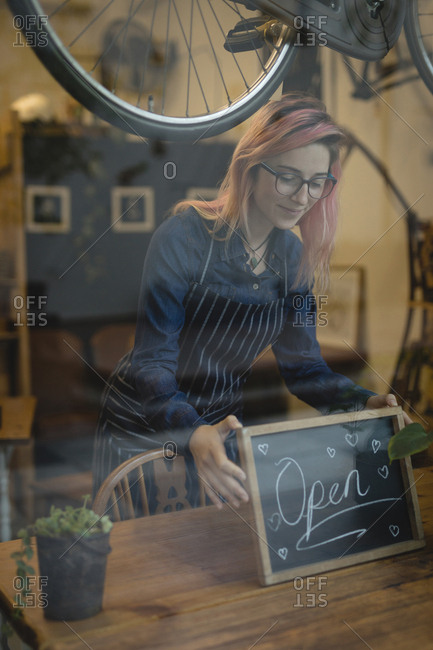 Barista placing a open signboard on the table at the coffee shop